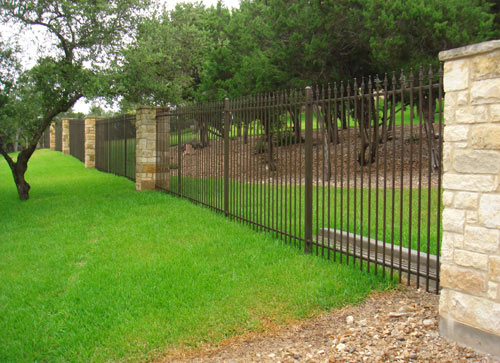 black metal fence and limestone poles