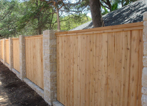 cedar wood fence with split rail top and stone beams
