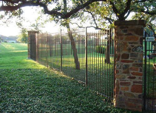 staggered 3 rail metal fence with stone pillars