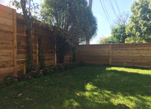 very tall backyard fence with horizontal boards stained