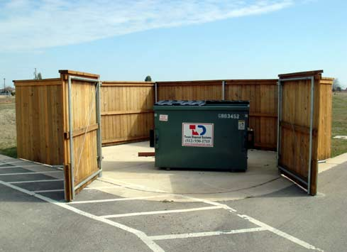 wood privacy fence around garbage dumpsters gate open